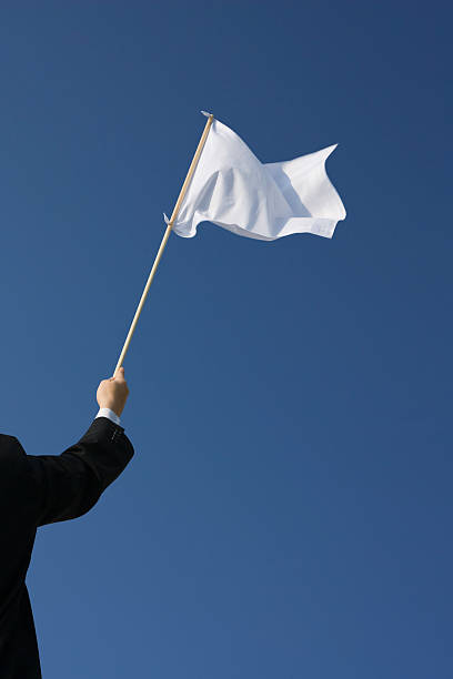 Businessman holding a white flag flutters in the wind against a blue sky.